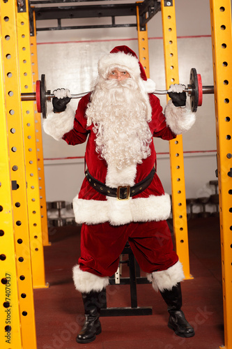canvas print picture Santa Claus lifting weights - training before Christmas