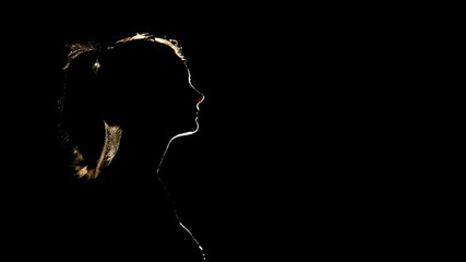 Silhouette of a woman who prays in the moonlight