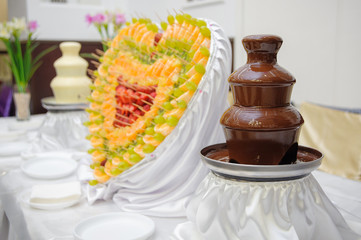 Chocolate fountain and heart from fruits at wedding reception