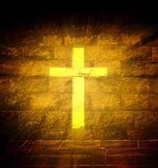 Christian religious cross with gold light ray on the brick wall