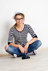 Pretty smiling female sitting at wall of empty room in headset