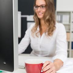 frau arbeitet am computer und hält eine tasse in der hand
