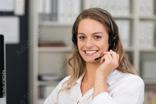 lächelnde mitarbeiterin telefoniert mit headset - 74072470