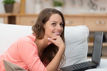 frau liegt auf dem sofa mit einem laptop