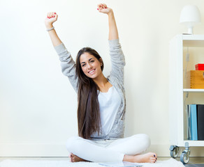 Beautiful young woman waking up and stretching arms at home.