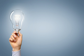 Hand mit Lampe vor leeren Hintergrund