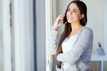 Beautiful young woman talking on the phone at home.