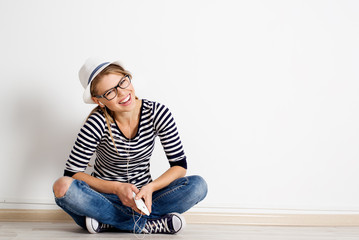 Laughing girl sitting on wooden flooring with smart phone