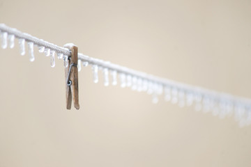 Wooden clothespin and icicles in row on the wire
