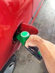 uomo che fa rifornimento di benzina ad un'uatovetrura rossa