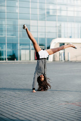 Girl standing on her arms upside down.