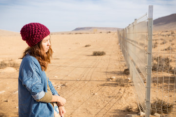 Girl standing next metal fencing.