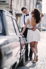 Сouple by the old car.