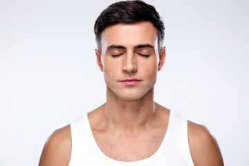 Handsome man with closed eyes over gray background