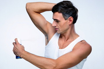 Handsome man using deodorant over gray background