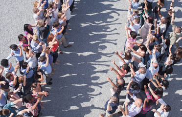 Two groups of people facing one another, arms raised