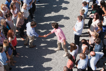 Two groups of people facing one another, two people shaking hands