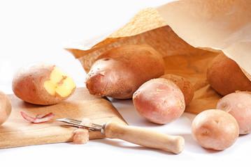 Peeling potatoes on white background