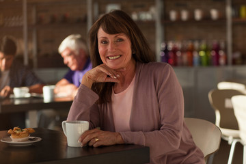Older woman having cup of coffee in cafe