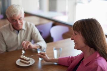 Older couple sharing dessert in cafe