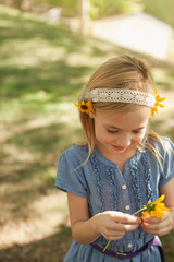 Girl playing with flowers outdoors