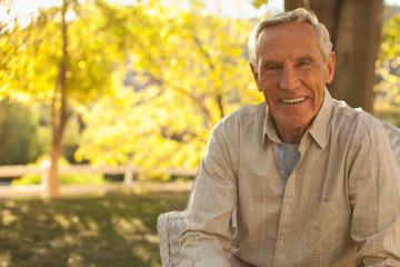 Smiling older man sitting outdoors