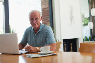 Older man using laptop indoors
