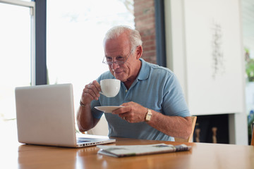 Older man having cup of coffee indoors