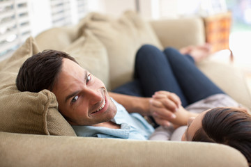 Man and woman holding hands on sofa