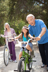 Older man helping granddaughter ride bicycle