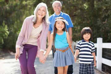 Older couple and grandchildren walking outdoors