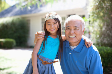 Older man and granddaughter standing outdoors