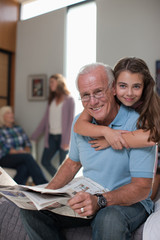 Girl hugging grandfather at home