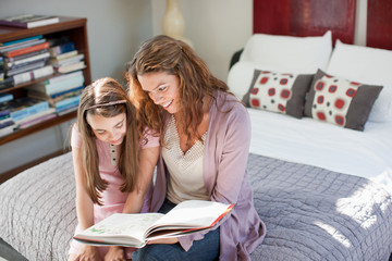 Mother and daughter reading on bed
