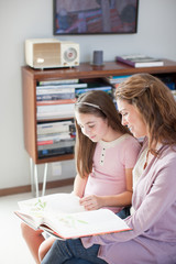 Mother and daughter reading together indoors