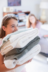 Girl carrying stack of folded towels