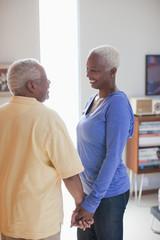 Smiling older couple holding hands indoors