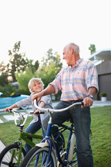 Older man and grandson riding bicycles outdoors