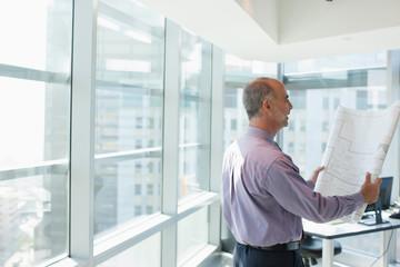 Businessman reading blueprint in office