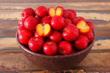 Red acerola - malpighia glabra, tropical fruit  in bowl on table