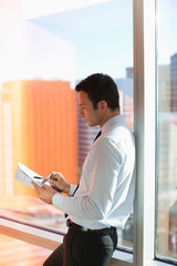 Businessman writing at window in office