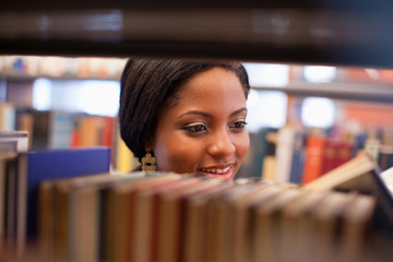 Smiling girl examining book in library