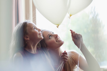 Sisters looking up at white balloons