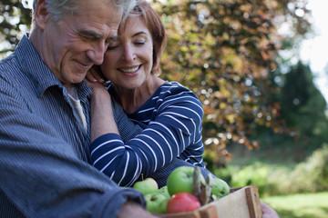 Happy senior couple with bushel of apples hugging