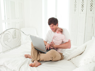 Father holding baby and using laptop