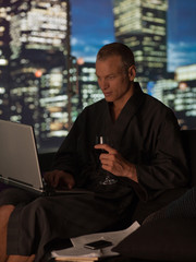 Man in bathrobe drinking wine and using laptop