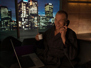 Man in bathrobe with laptop drinking coffee and talking on telephone