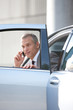 Businessman getting out of car talking with cell phone