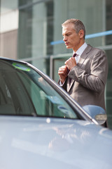 Businessman adjusting necktie outdoors