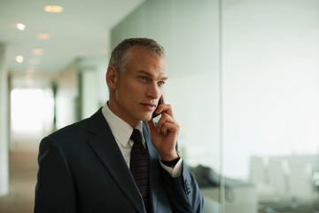 Businessman talking on cell phone  in office corridor